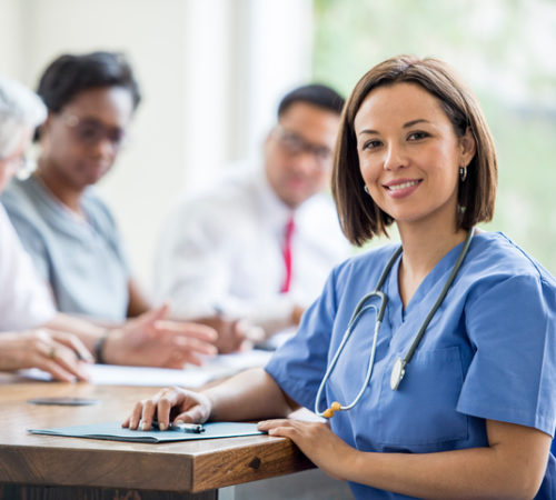 A multi-ethnic group of medical staff are indoors in a hospital. They are wearing medical clothing. They are sitting at a table and writing reports together. A Caucasian female doctor is turned to smile at the camera.